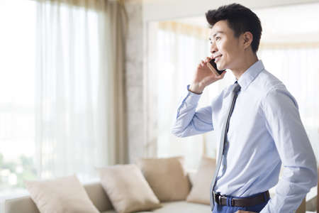 executive apartment: Young businessman talking on cell phone at home