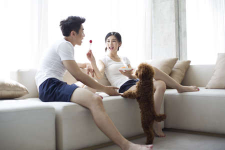 couple on couch: Happy young couple eating fruit salad on sofa