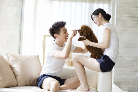 couple on couch: Young couple playing with a pet poodle at home