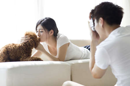 couple on couch: Young couple taking photos at home