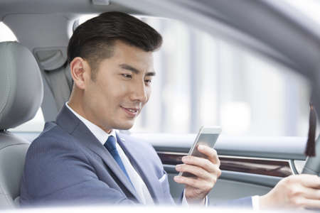 transportation: Confident businessman holding smart phone in a car