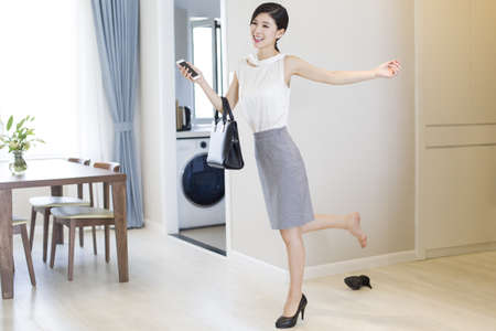 Young woman taking off her high heels after work LANG_EVOIMAGES