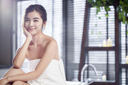 self conscious: Beautiful young woman wrapped in towel