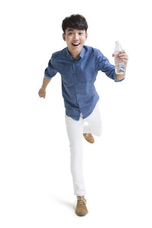Happy young man running with a bottle of water LANG_EVOIMAGES
