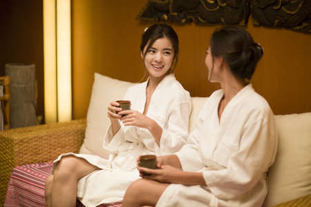 self conscious: Beautiful young women talking in spa center