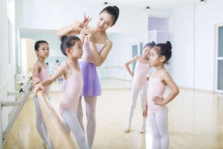 Young ballet instructor teaching girls in ballet studio