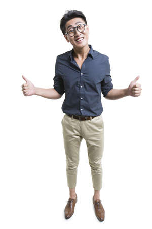 Happy young man doing thumbs up LANG_EVOIMAGES