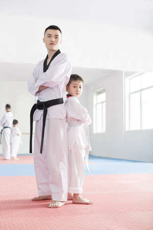 full length mirror: Young instructor and boy in taekowndo gymnasium