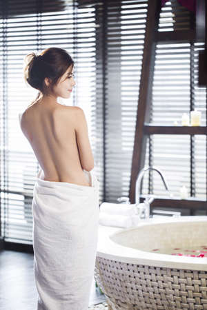 self conscious: Rear view of beautiful young woman wrapped in towel LANG_EVOIMAGES