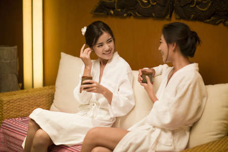 oriental bathrobe: Beautiful young women talking in spa center