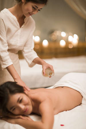 self conscious: Young woman receiving back massage at spa center