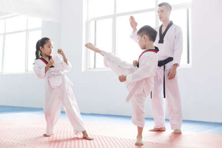 dueling: Young instructor teaching children Tae Kwon Do LANG_EVOIMAGES