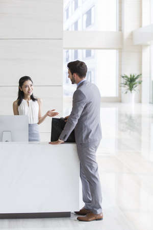 Businessman talking with receptionist