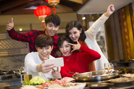chafing dish: Young friends taking self portrait with a smart phone LANG_EVOIMAGES