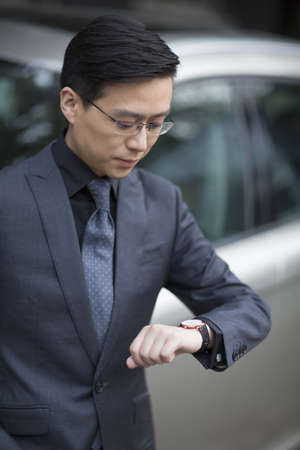Mid adult businessman checking the time on wristwatch