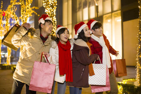 christmas spending: Happy young friends shopping for christmas