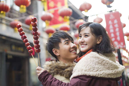 Young couple with candied haw berries celebrating Chinese New Year LANG_EVOIMAGES