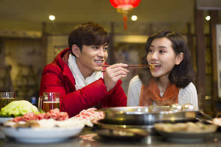 chafing dish: Young couple having dinner in hotpot restaurant LANG_EVOIMAGES
