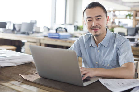 technology: Male architect working with laptop in the office