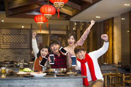 Young friends showing smart phones in restaurant