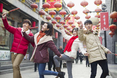 Young friends with candied haw berries celebrating Chinese New Year LANG_EVOIMAGES