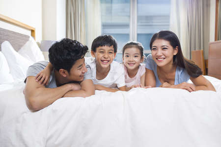 girl in full growth: Cheerful young family on a bed LANG_EVOIMAGES