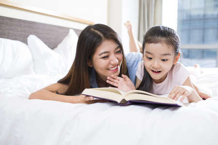 girl in full growth: Little girl reading a book with mother LANG_EVOIMAGES