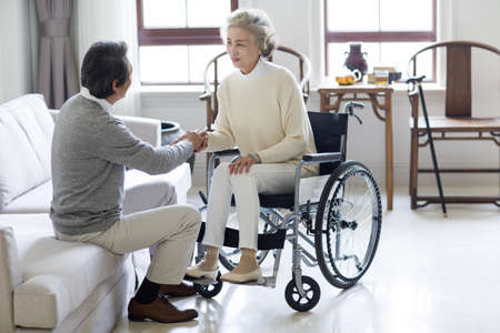 physical impairment: Senior man taking care of wife in wheel chair