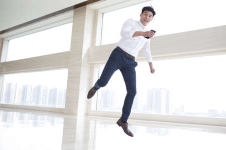 legs apart: Cheerful young businessman jumping in office building