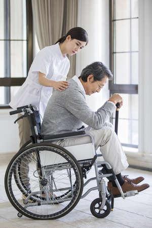 Nursing assistant taking care of senior man in wheel chair LANG_EVOIMAGES