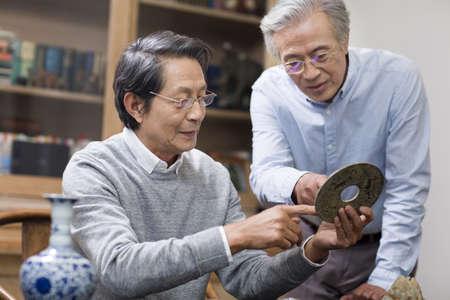 antique vase: Senior men admiring antiques