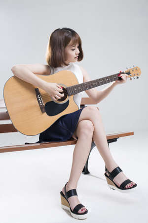 soloist: Young woman playing guitar