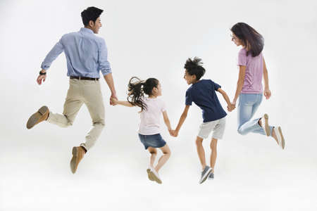 Cheerful young family jumping LANG_EVOIMAGES