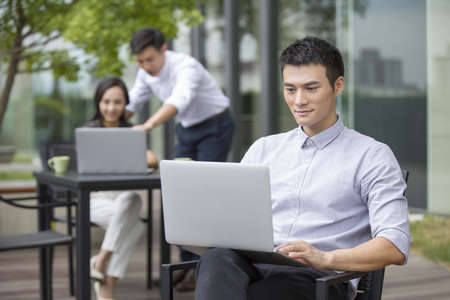 legs crossed at knee: Young businessman using laptop outdoors LANG_EVOIMAGES