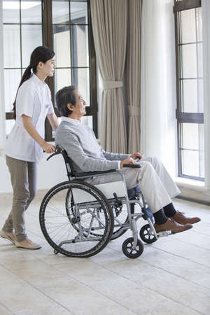 physical impairment: Nursing assistant taking care of senior man in wheel chair LANG_EVOIMAGES