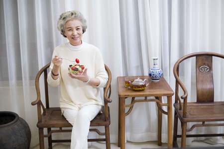 legs crossed at knee: Happy senior woman eating salad