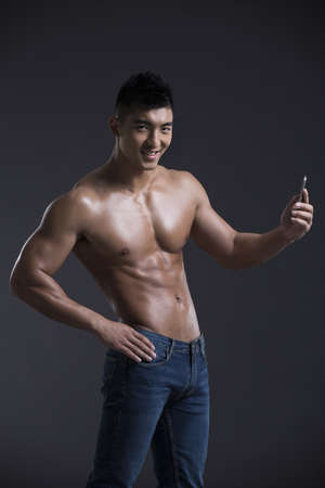 metrosexual: Young muscular man with a smart phone LANG_EVOIMAGES