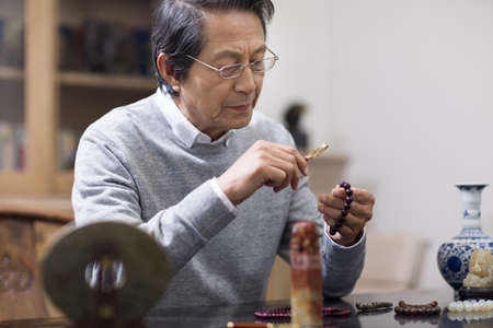 indian style sitting: Senior man admiring antiques
