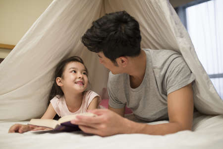 girl in full growth: Little girl reading a book with father