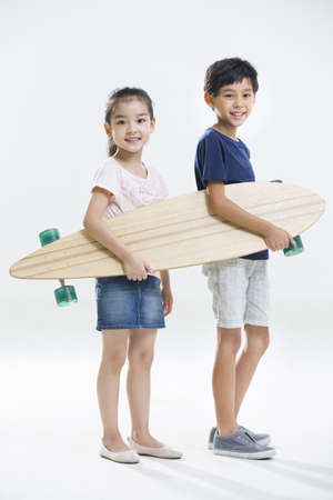 girl in full growth: Cute little boy and girl playing with skateboard LANG_EVOIMAGES