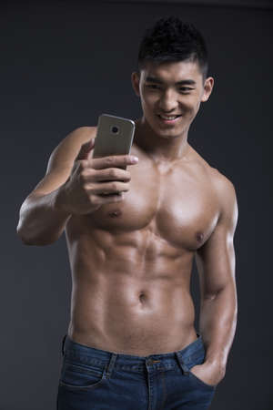 Young muscular man using smart phone