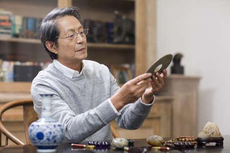 antique vase: Senior man admiring antiques