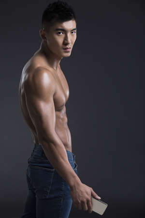 Young muscular man with a smart phone LANG_EVOIMAGES
