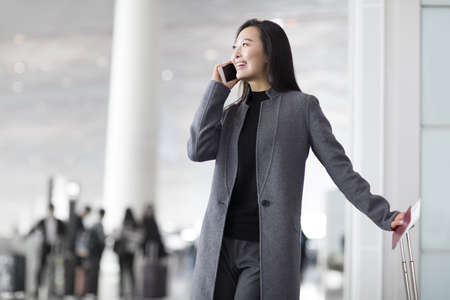 incidental people: Businesswoman talking on cell phone at the airport