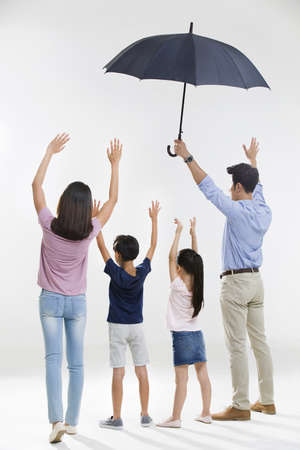 girl in full growth: Cheerful young family with an umbrella LANG_EVOIMAGES