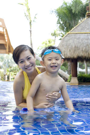 one parent: Mother and son having fun in the pool LANG_EVOIMAGES