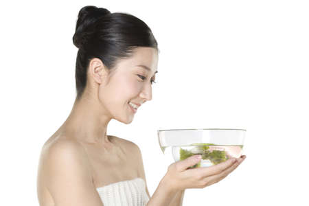 A young woman holding a bowl of flowers floating in water