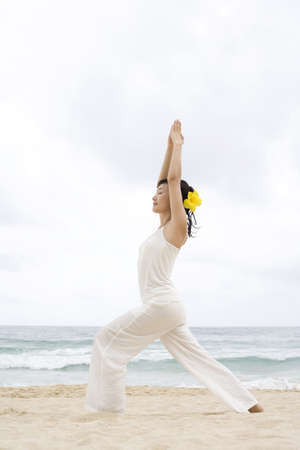 A woman practicing yoga at the beach