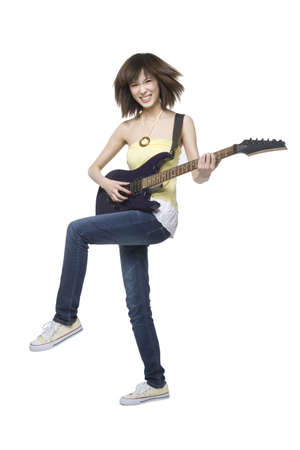 roll out: Young woman playing an electric guitar