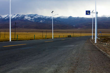 swerving: Road going through field into Qilian Mountain in Qinghai province,China